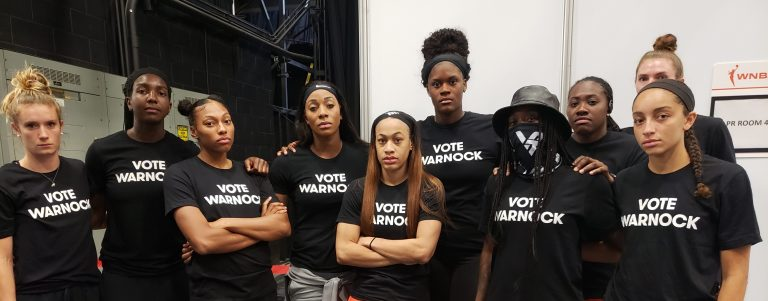 Atlanta Dream's Elizabeth Williams and teammates wearing Vote Warnock T-shirts