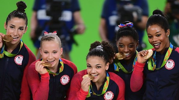 The U.S. womens gymnastics team celebrates winning gold at the 2016 Rio Olympics