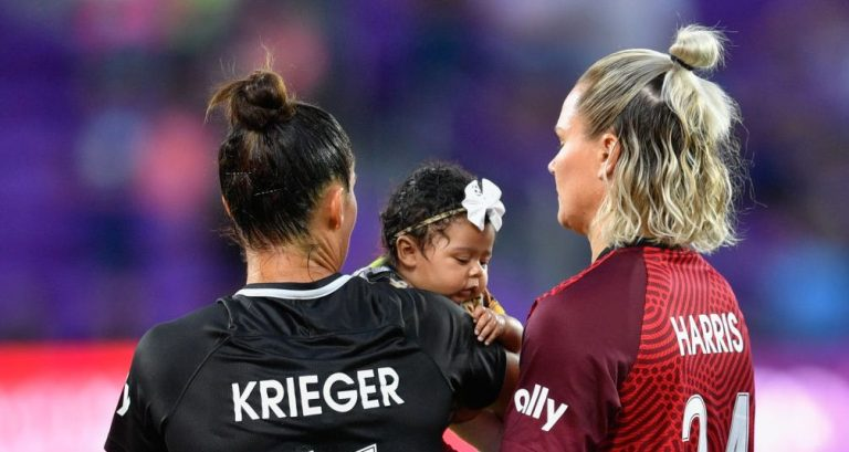 Ali Krieger #11 (left) and Ashlyn Harris #24 (right) of the Orlando Pride hold their daughter Sloane after a game between Washington Spirit and Orlando Pride.