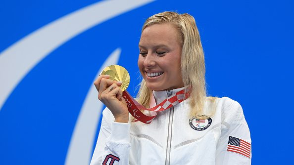 Jessica Long posing on the podium with her gold medal after winning the women's SM8 200m IM