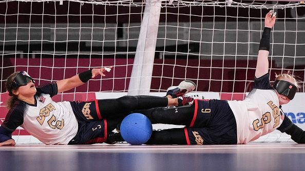 Two members of the U.S. women's goalball team - Amanda Dennis (left) and Marybai Huking (right) block the ball during a preliminary group match at the 2021 Tokyo Paralympics.