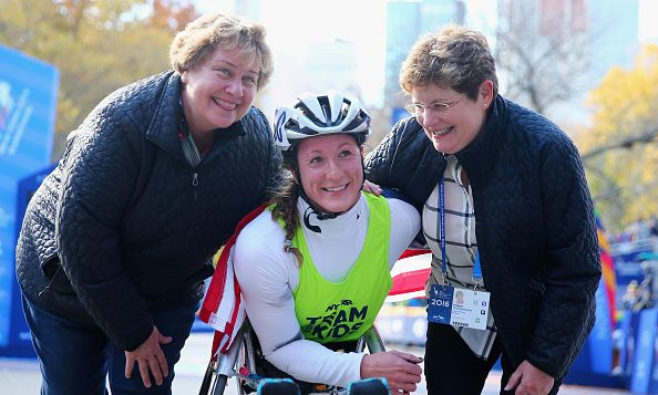 Tatyana McFadden celebrates with her moms, Bridget O'Shaughnessey (R) and Debbie McFadden (L), after winning the women's wheelchair division at the 2016 TCS New York City Marathon. (Photo by Elsa/Getty Images)